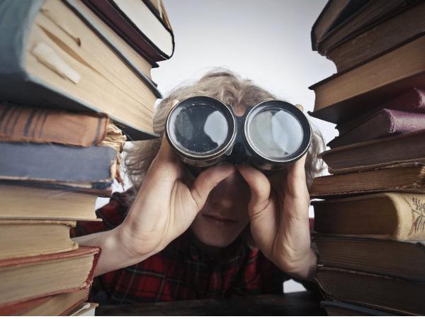 History buff boy with binoculars sitting between books