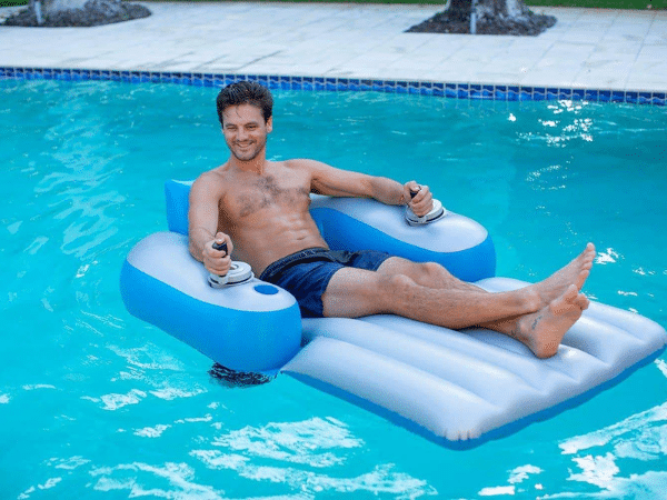 Man smiling while sitting on motorized pool float in a pool