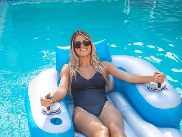 Women smiling while riding motorized pool lounger